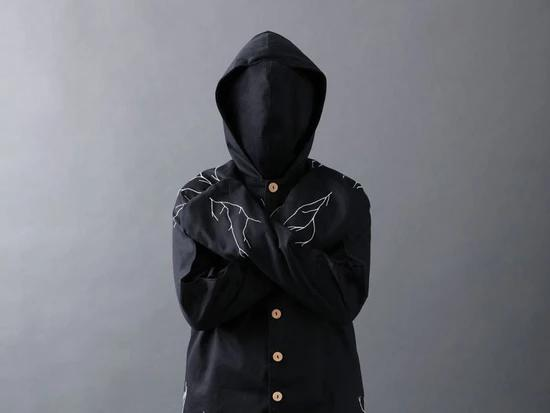 The Infinity Body Suit is a black, hooded body suit that also includes a black face mask. It has light brown wooden buttons. Across the shoulders there is a white, embroidered design resembling tree branches.