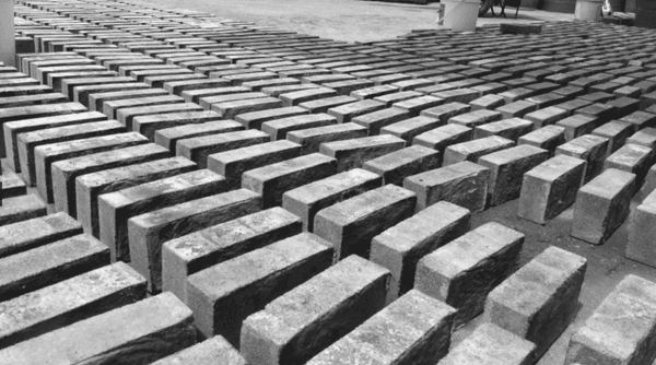 Lines of gray biocement bricks lined up on the ground.