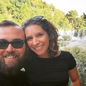 Jason and Marisa standing in front of a waterfall in Krka, Croatia