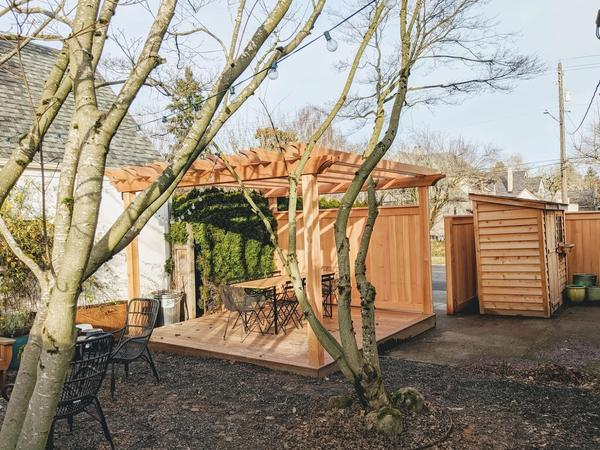 Image of a wood pergola and patio, a new fence, and a barn style shed in our backyard.