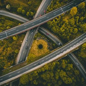 Aerial photo of intersecting freeway roads surrounded by trees.