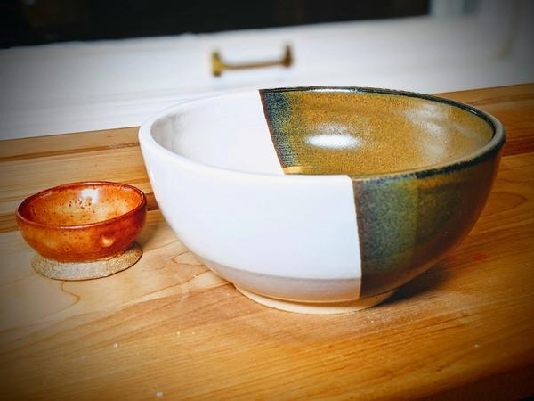 A picture of my first, very small, ceramic bowl. It's quite shallow and can hold some salt and a very tiny spoon. The other bowl is much larger, and can be used as a noodle bowl.