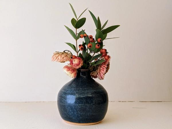 dark blue bud vase with assorted dried flowers