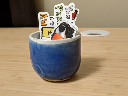 Small blue cup I made that is holding several stickers