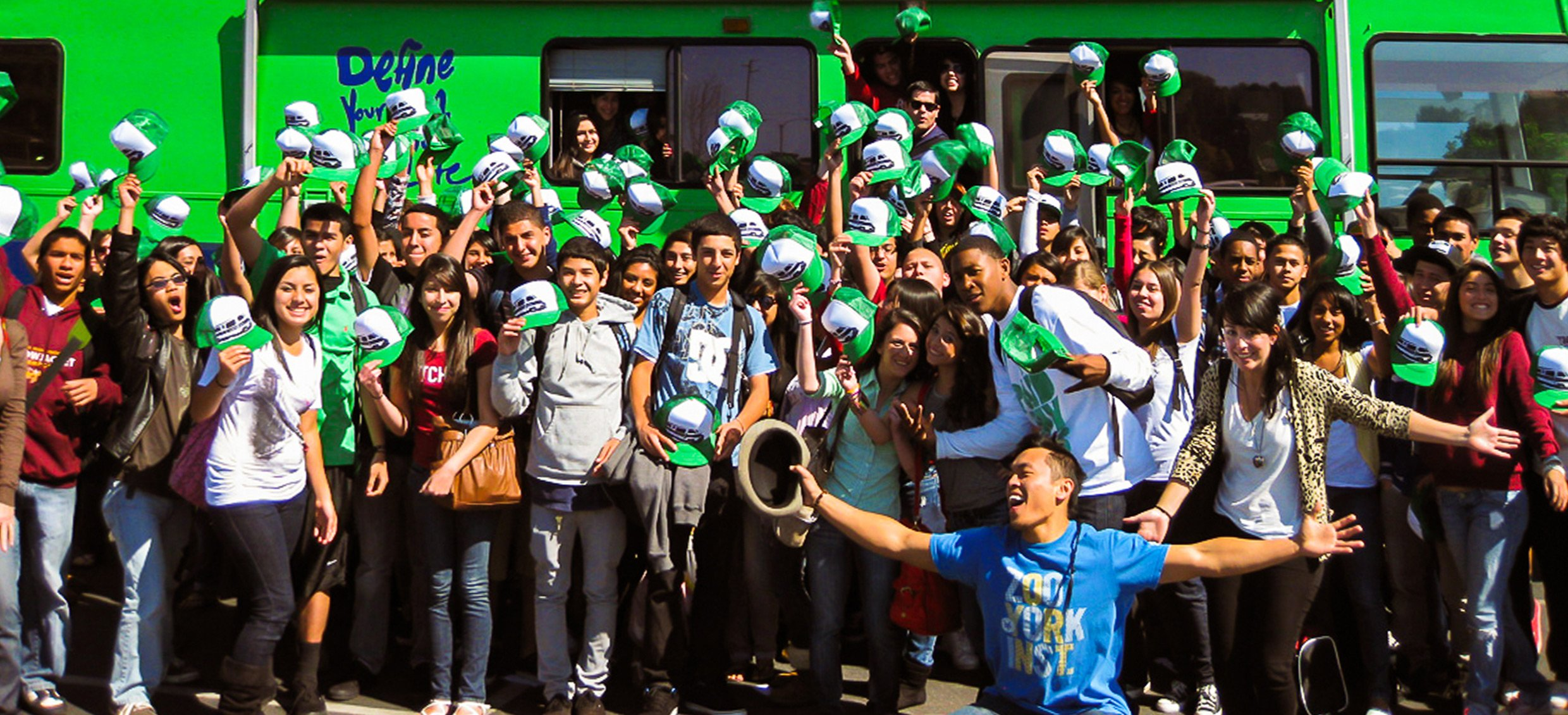 A group of students show off their Roadtrip Nation swag in front of the green RV