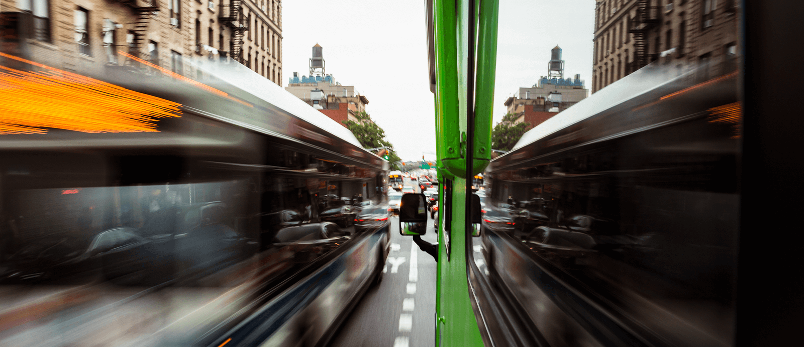 Cars rush by the Roadtrip Nation green RV as it drives down a busy city street.