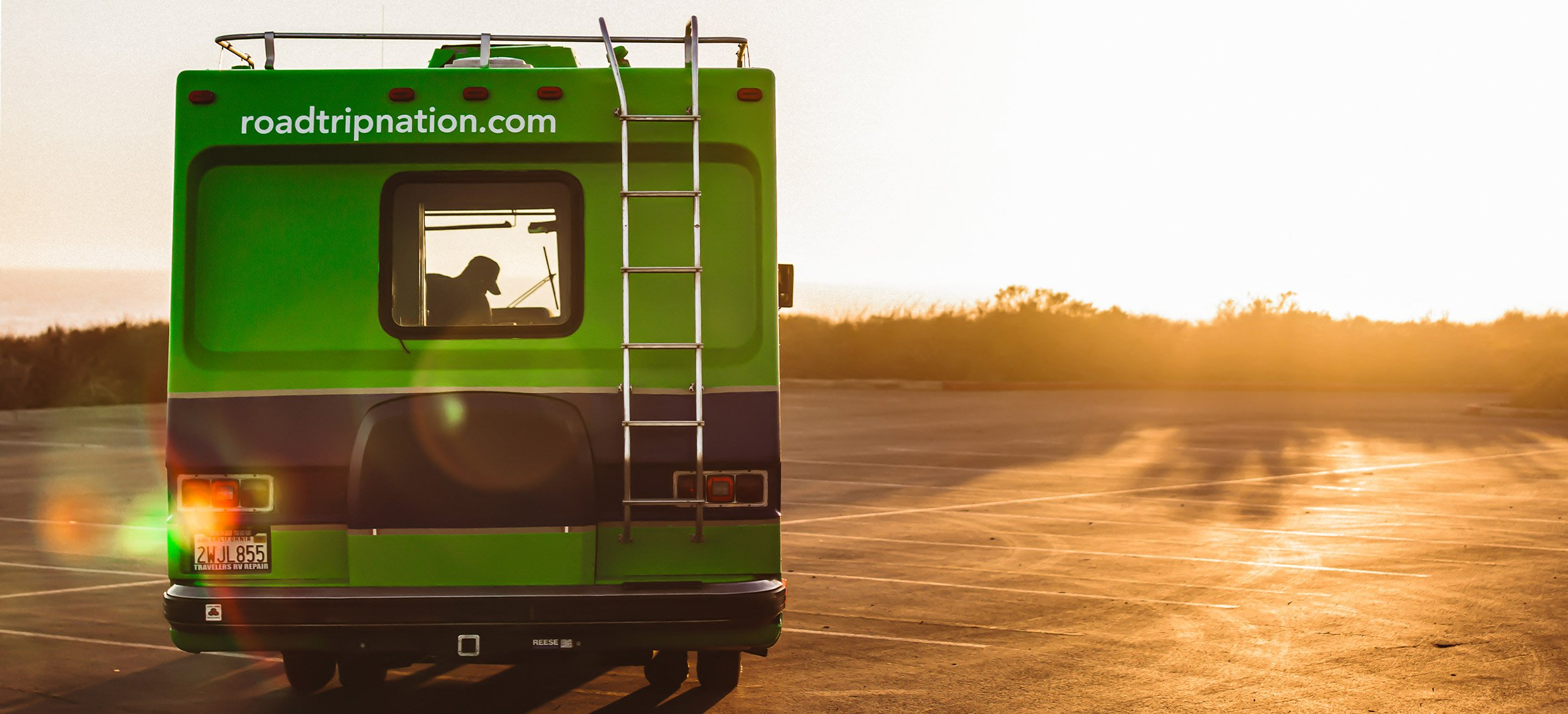 The Roadtrip Nation green RV parked in front of the sunset during golden hour.