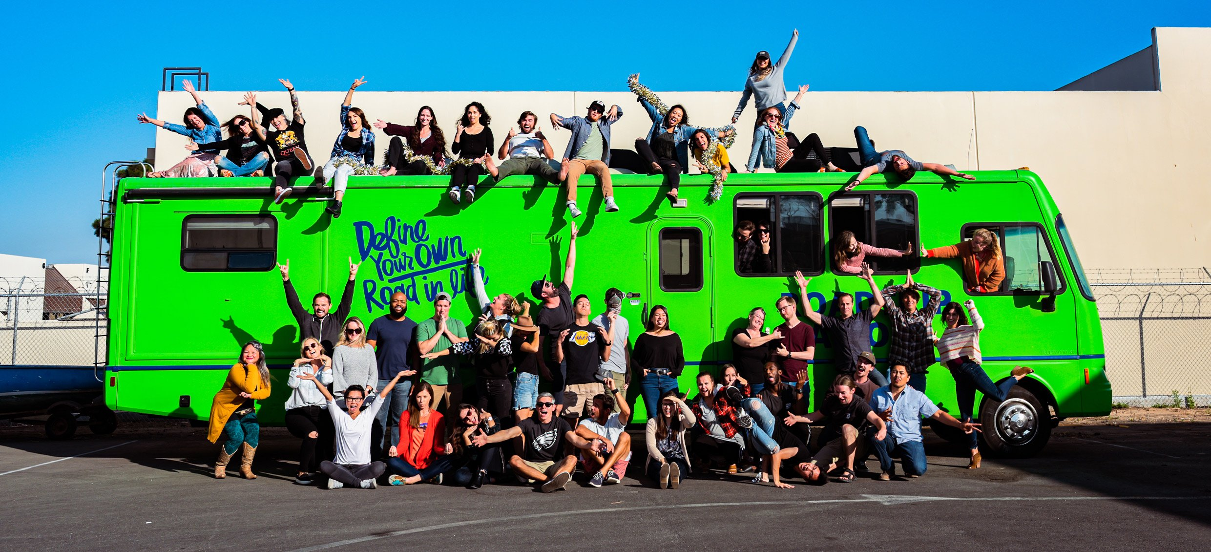 The Roadtrip Nation staff does a goofy pose in front of the green RV.