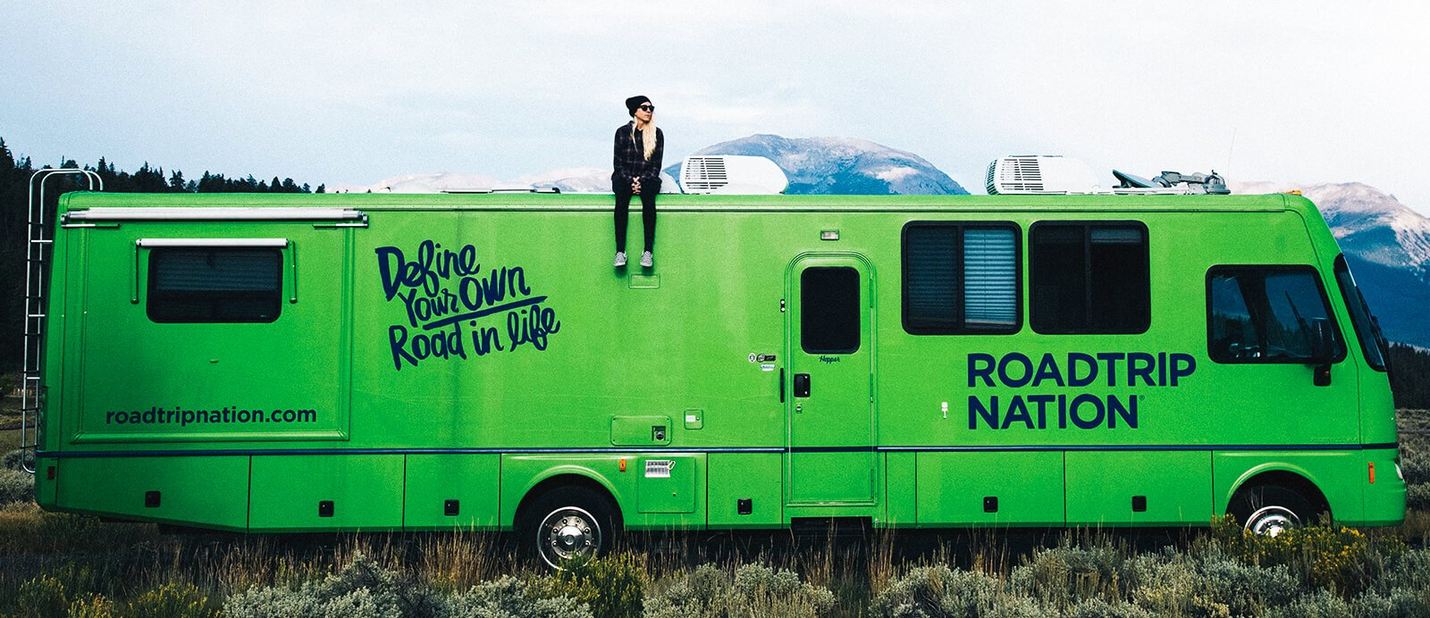 A young woman sits on top of the Roadtrip Nation green RV.