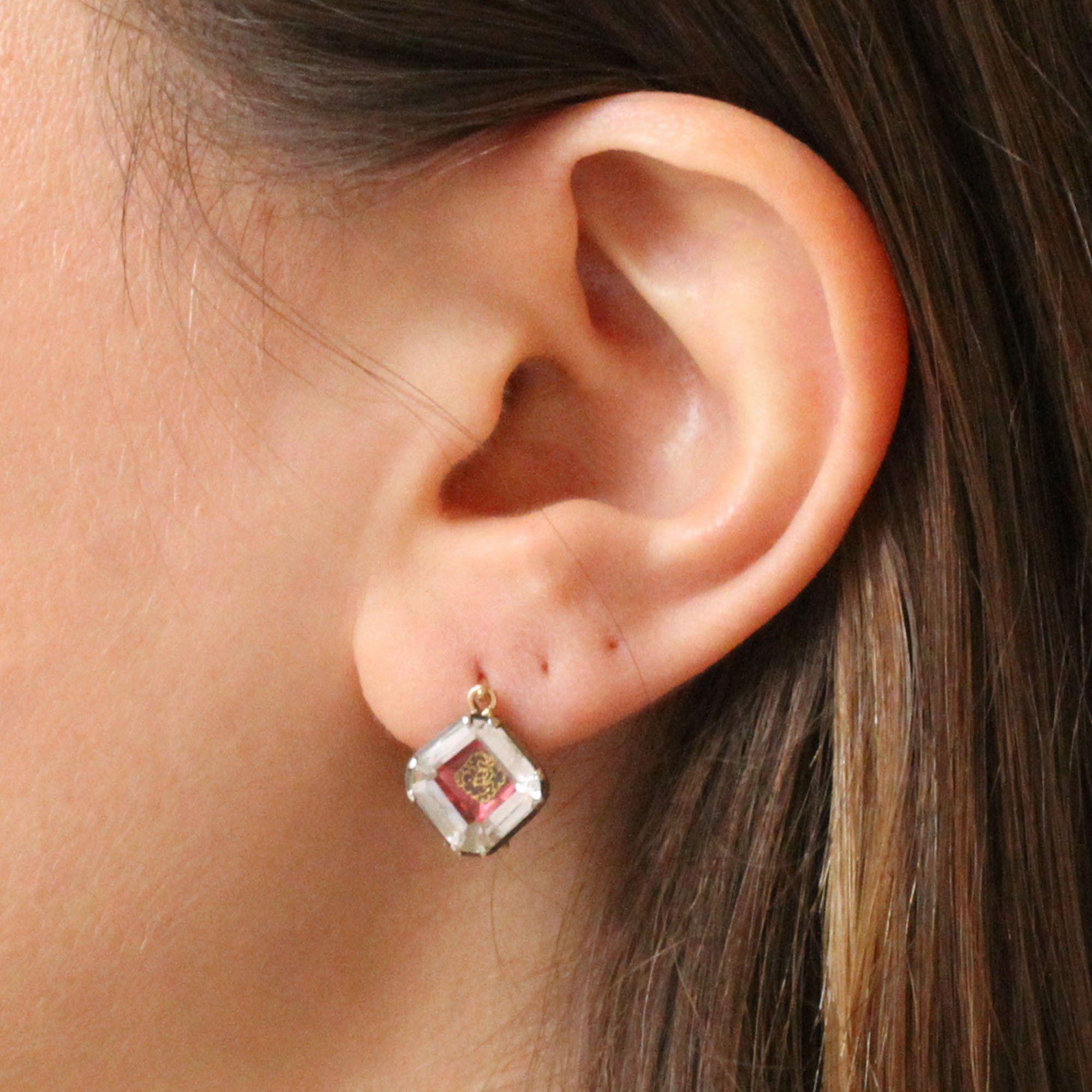 Pink Stuart Crystal earrings worn on an ear