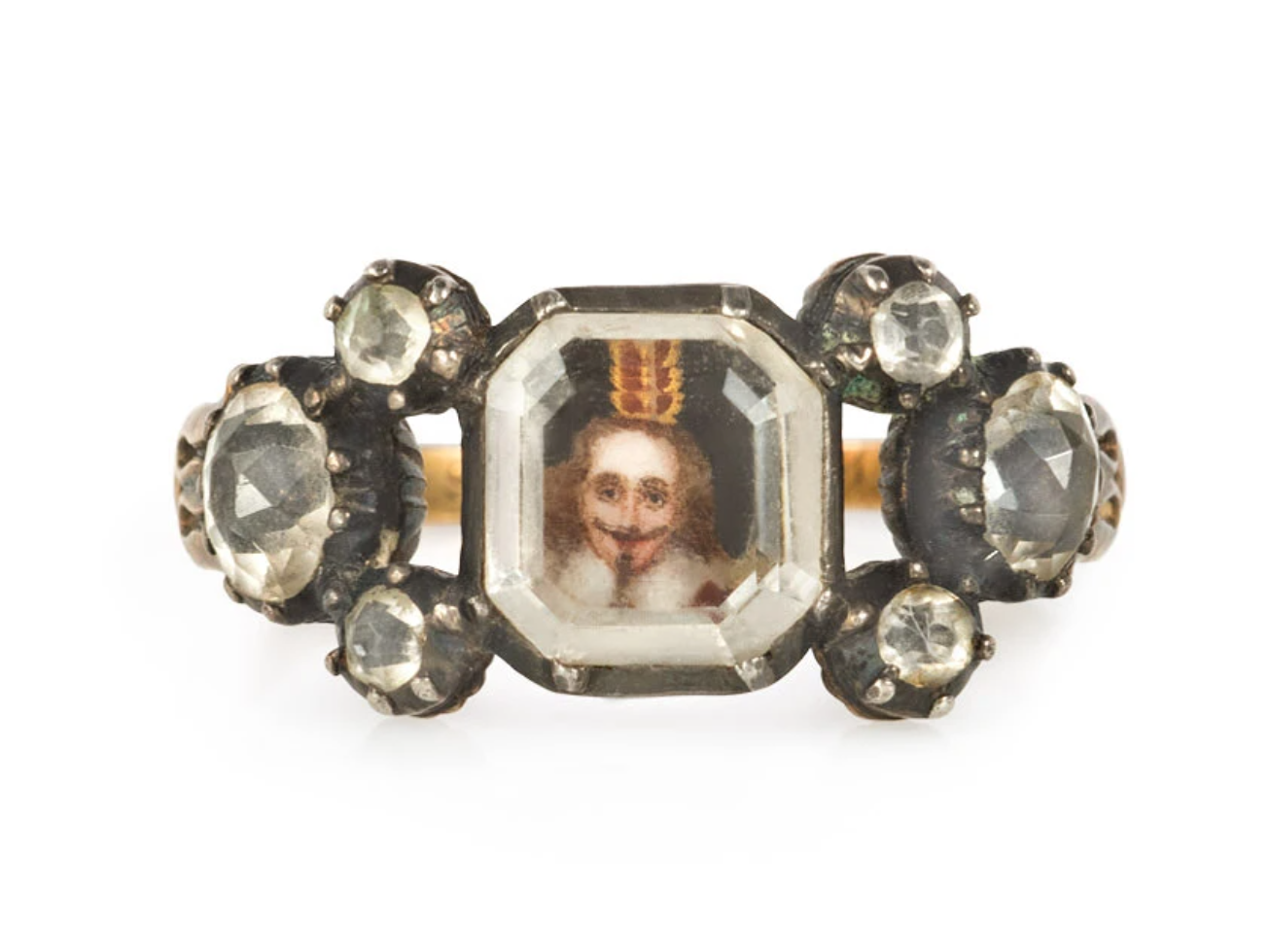 An antique Stuart crystal ring centering on a flat octagonal quartz revealing a miniature royal portrait, flanked on both sides by three old cut quartz and gold foliate shoulders, with engraved upper shank and under gallery, in 18k. Inscribed W. Mc 1738