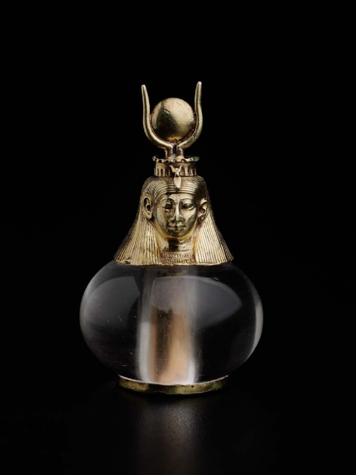 Photograph of Egyptian round crystal container with a gold Hathor headed top.