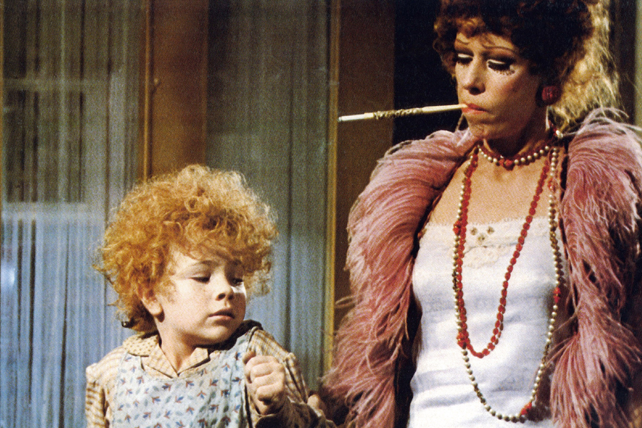 A photo still from the 1982 movie Annie of Miss Hannigan holding young Annie's arm.