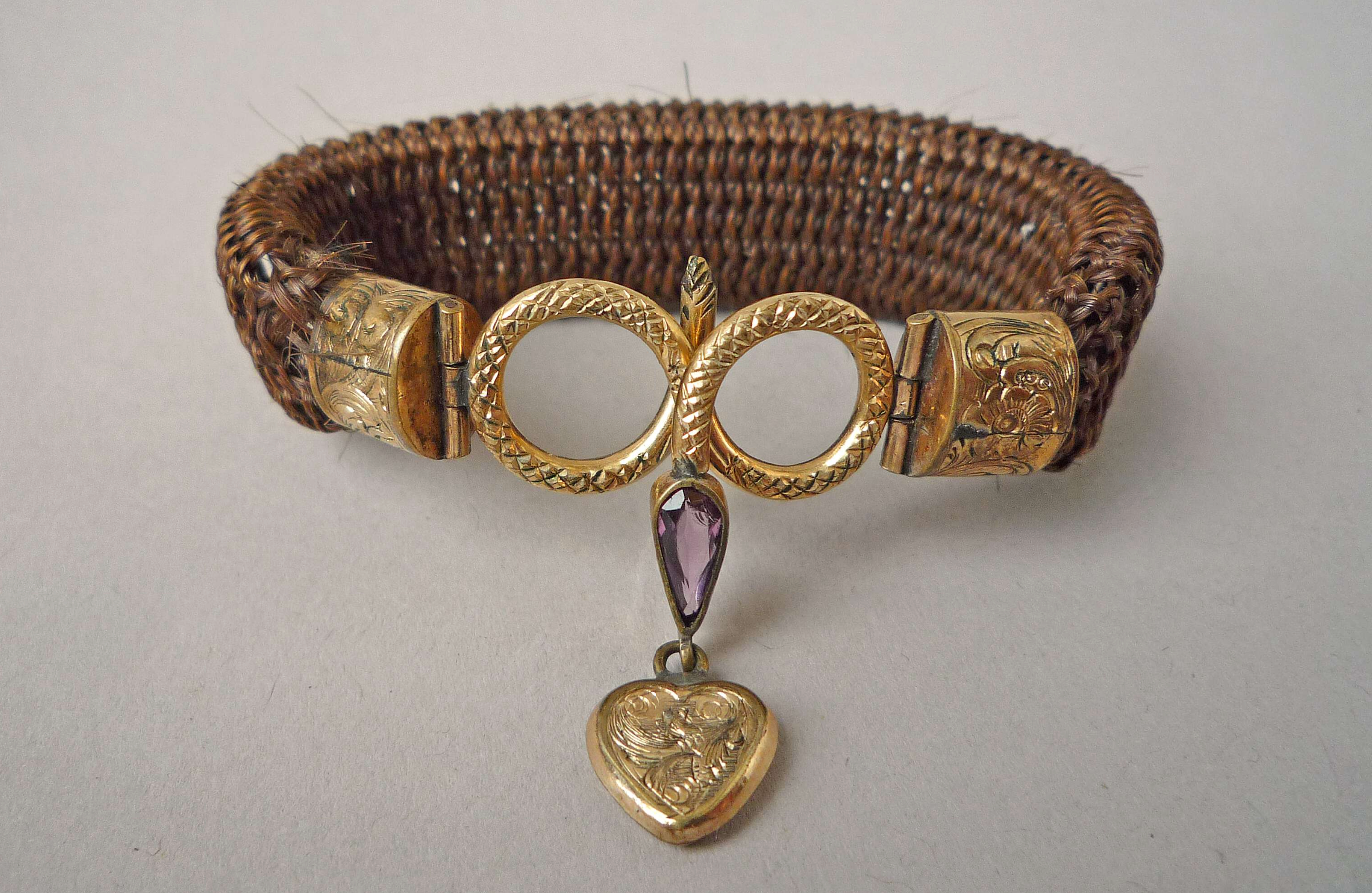 Bracelet of flat plaited hair with engraved gold ends and coiled gold serpent clasp with amethyst drop and small pendant gold heart, thought to be the work of Antoni Forrer, c1850-1870, British Museum