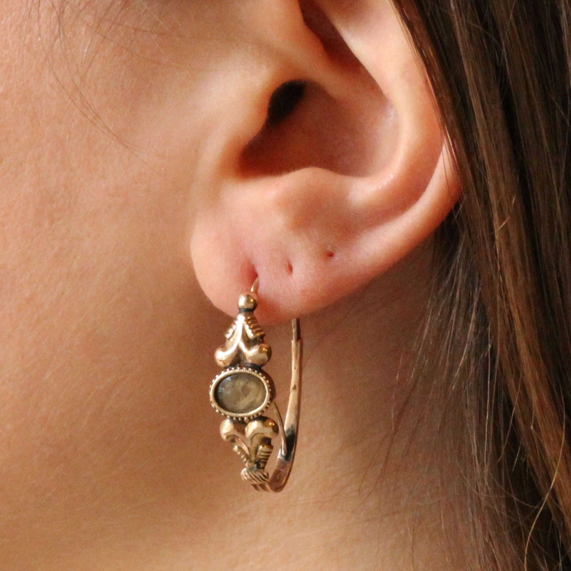 Closeup of someone wearing the Poissarde Earrings with Hair Lockets