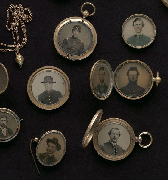 A photograph of an assortment of lockets from the 1800s, all open to reveal tintype photographs of Civil War soldiers inside.
