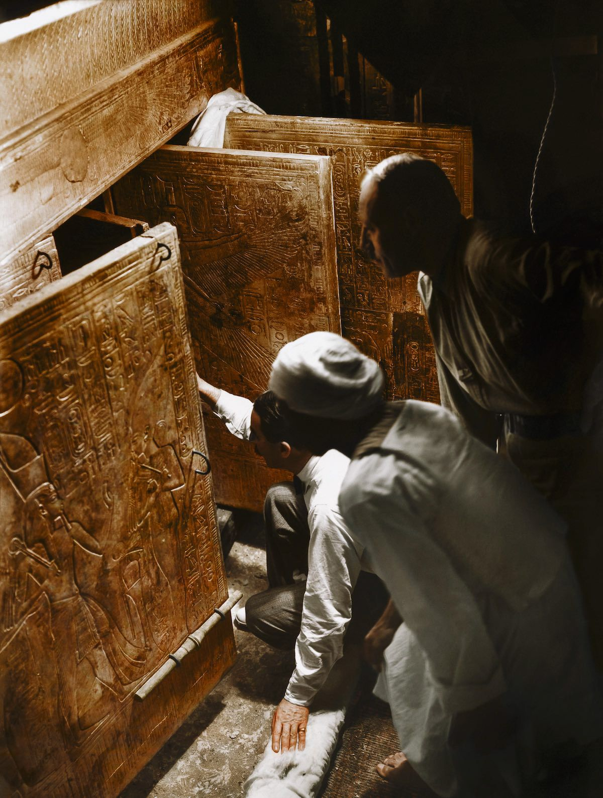 Howard Carter (center) looking inside an Egyptian tomb, colorized by Dynamichrome.