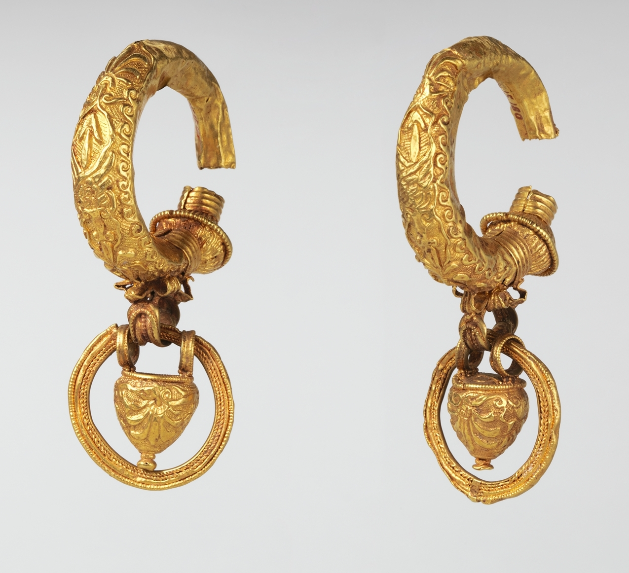 The pendant rings that hang from these hollow gold earrings are thought to have contained perfume. 4th-3rd century B.C., Metropolitan Museum of Art.