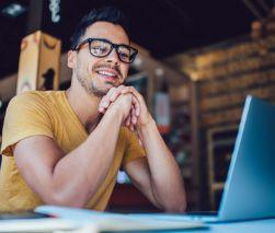 happy laptop guy in log cabin