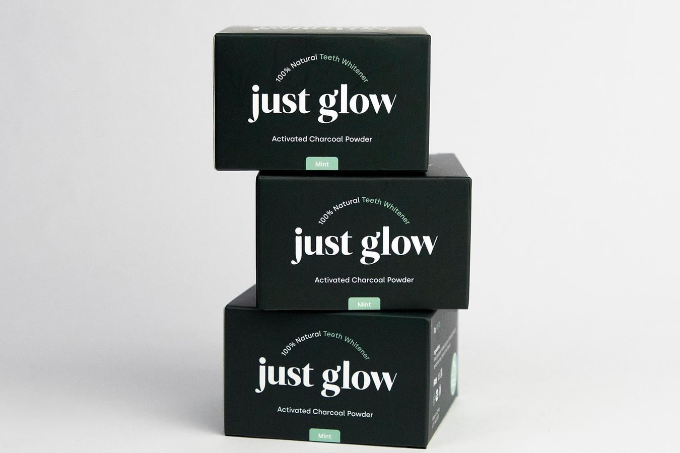 a stack of Just Glow Activated Charcoal powder
