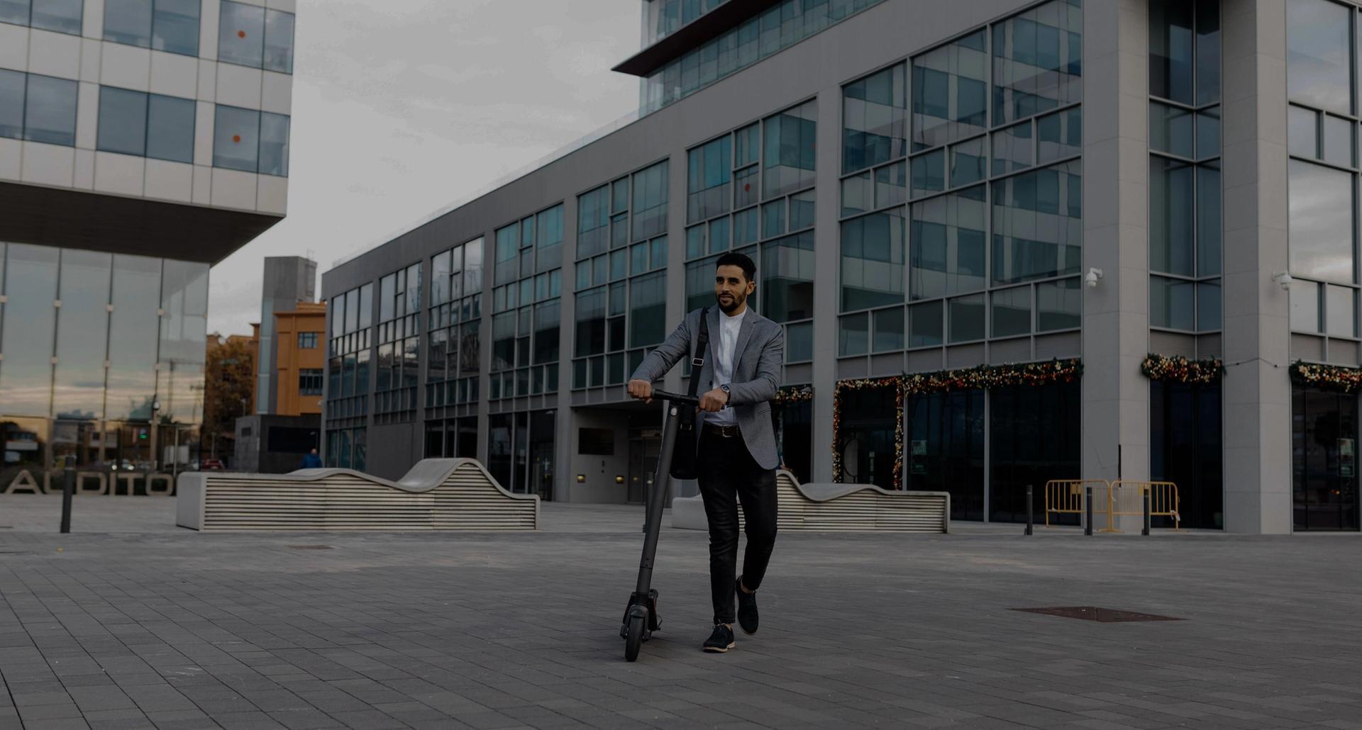 Mies kuljettamassa Augment.eco skuuttia