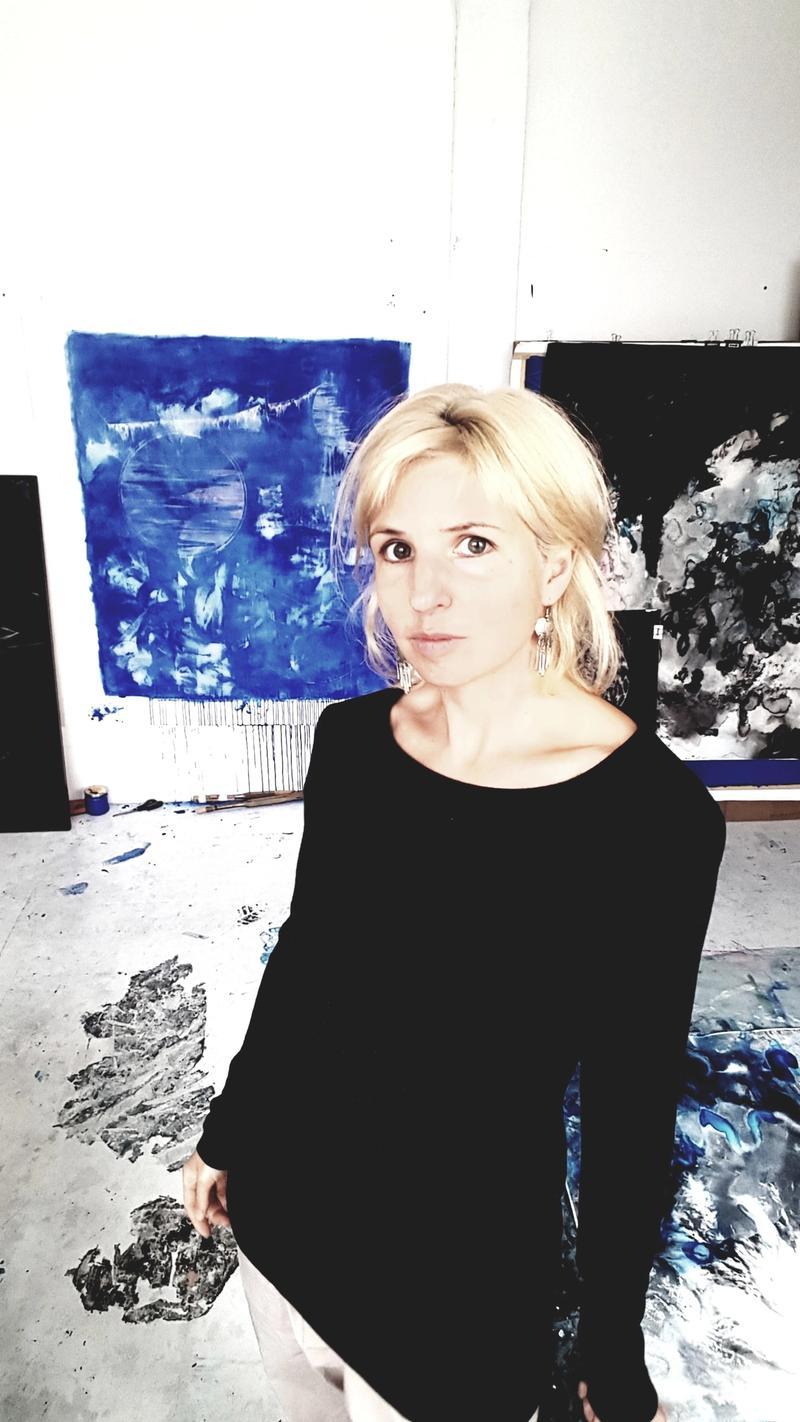 Portraitfoto von Jana Schumacher in ihrem Atelier zwischen Kunstwerken