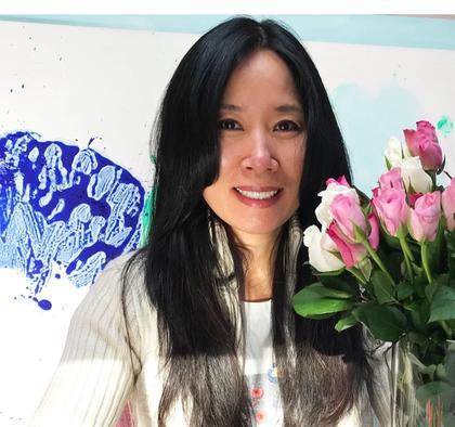 Portrait der Künstlerin Miye Lee, neben ihr eine Malerei und ein Blumenstrauß