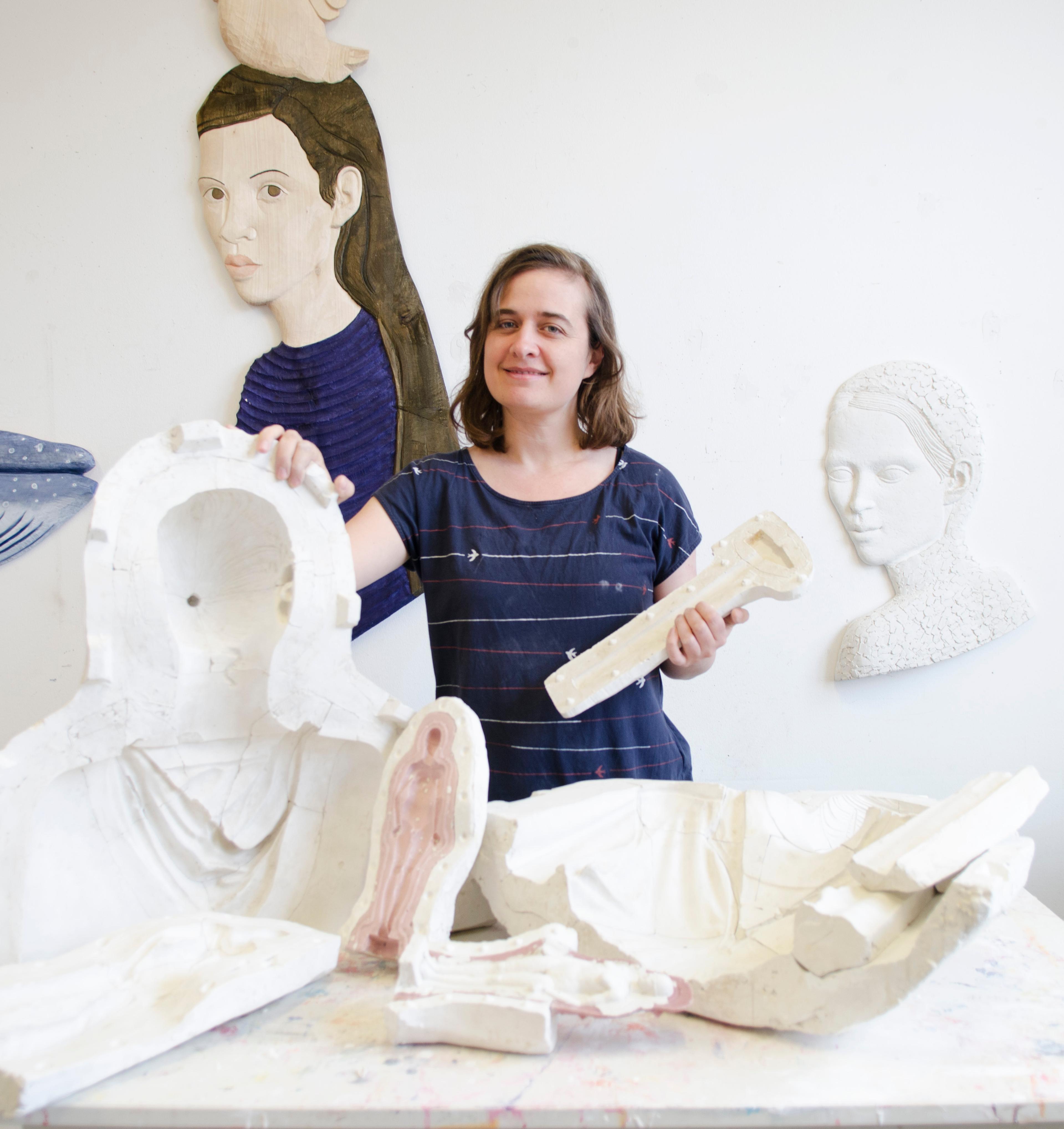Portraitfoto der Künstlerin Isabel Ritter, vor ihr Teile ihrer Skulpturen