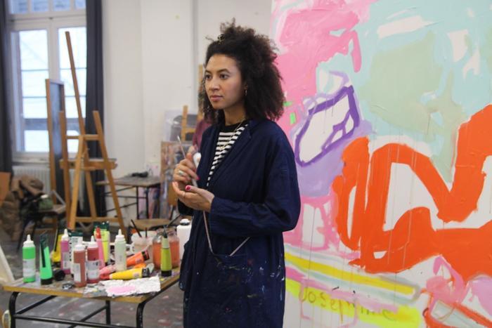 Die Künstlerin Joséphine Sagna bei der Arbeit, in ihrem Atelier, vor einem Tisch mit Farben und einem ihrer Werke