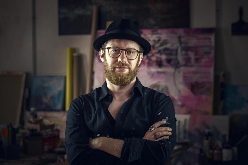 Portraitfoto des Künstler Patrick Hartl, mit verschränkten Armen in seinem Studio vor Arbeiten im Hintergrund