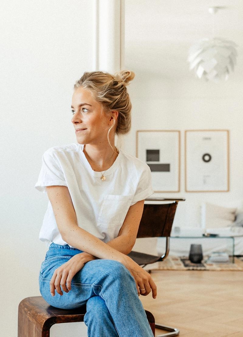 Portraitfoto von Anabelle von Georg, sitzend, im Hintergrund eine Couch und große Bilder