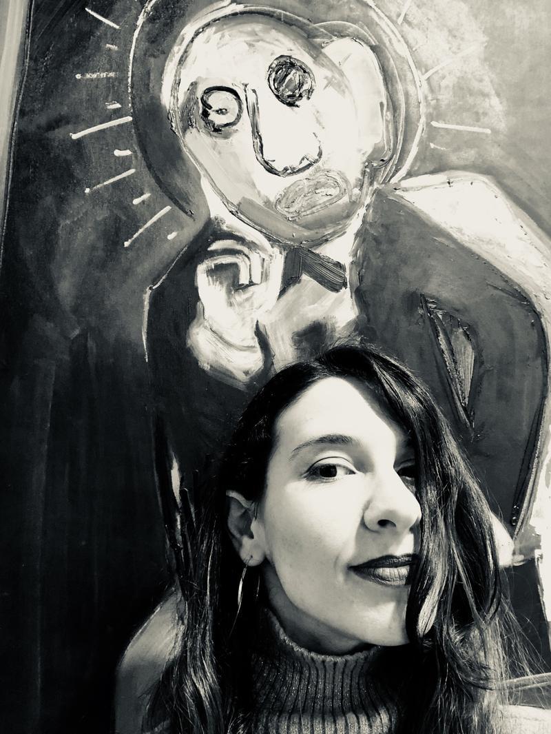 Schwarz weiß Portrait der Künstlerin Penny Monogiou, vor einem ihrer Bilder