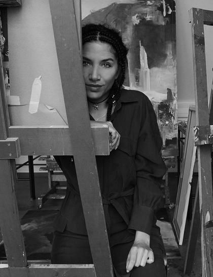 Portraitfoto von Christine Brey halb verdeckt hinter einer Staffelei mit Leinwand