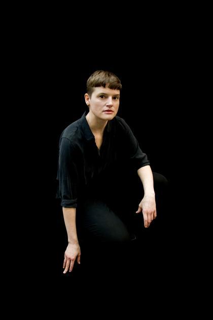 Portraitfoto von Isabell Kamp vor schwarzem Hintergrund