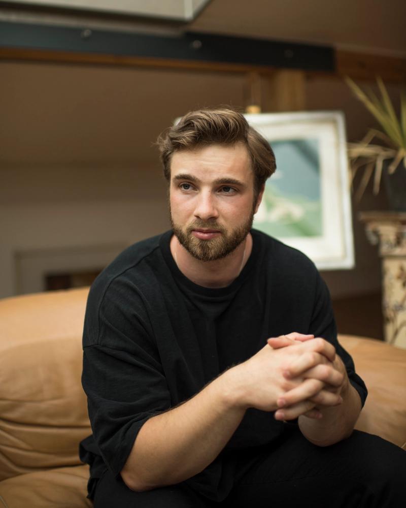 Portrait von Stephan Hohenthanner, auf einer braunen Couch vor zwei Kunstwerken