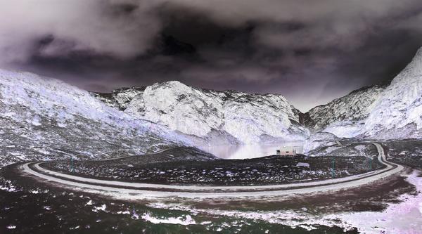 Ein Negativfoto einer Berglandschaft. Eine kurvige Straße läuft durch den Vordergrund.