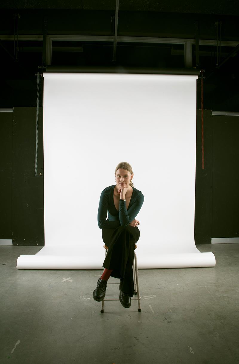 Portraitfoto Theresa Maria Forthaus, junge Frau auf einem Hocker vor einer weißen Leinwand