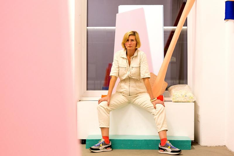 Portrait Petra Gell, auf einer Fensterbank sitzend in ihrem Atelier