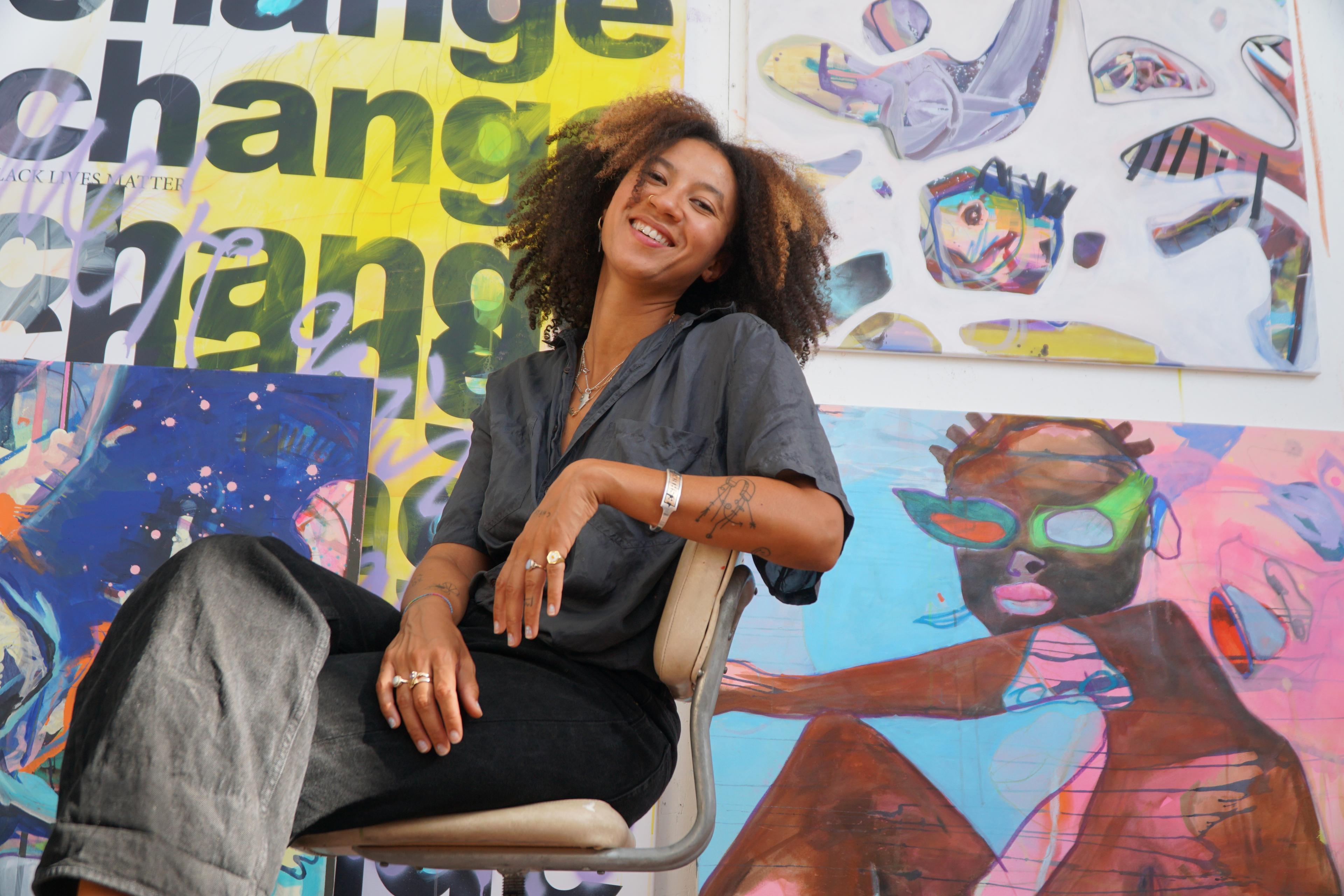 Portraitfoto von Joséphine Sagna, sitzend vor eine Auswahl ihrer Arbeiten