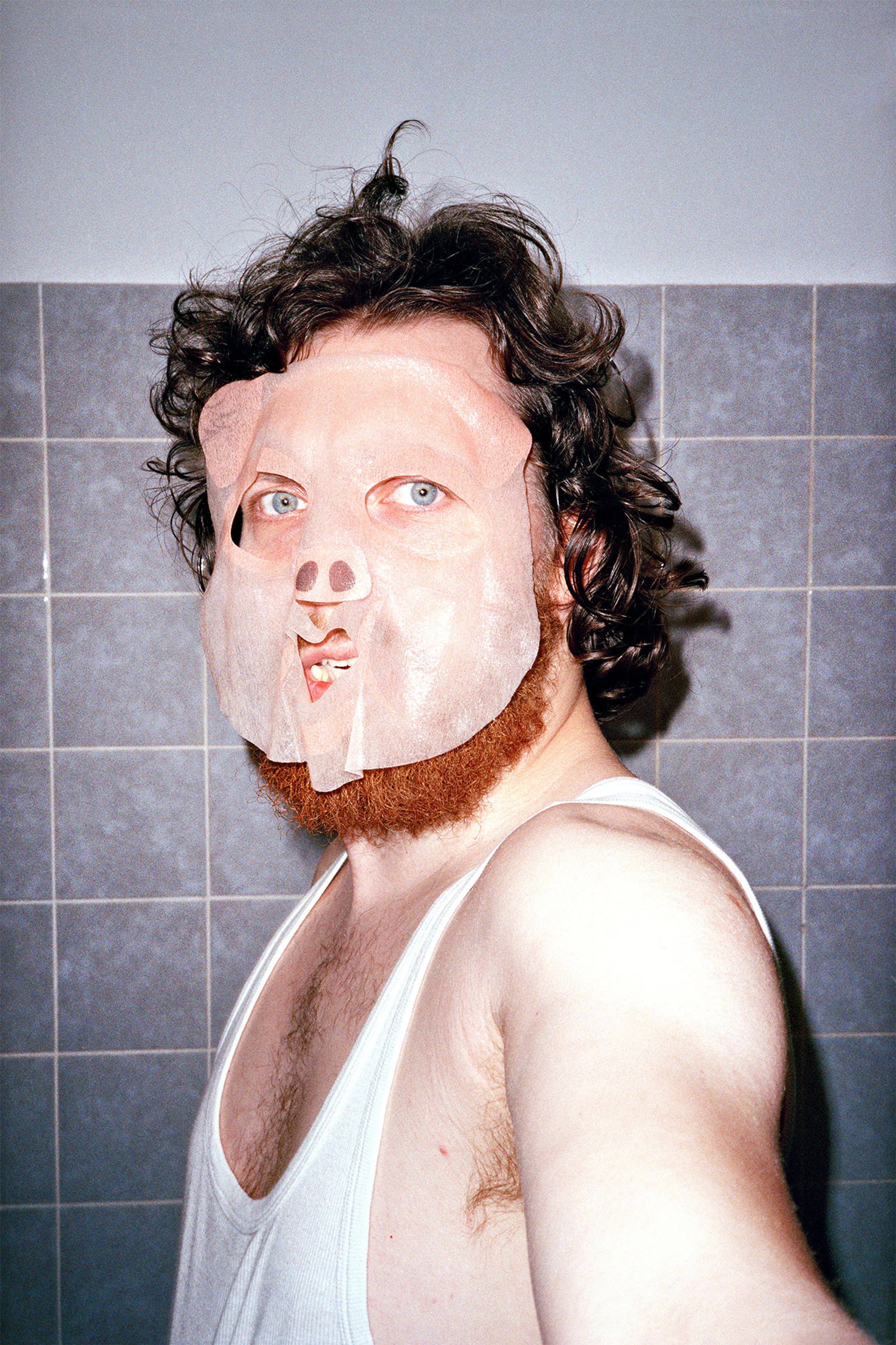 Portraitfoto Steve Braun, Mann im Unterhemd vor grauen Fließen mit Locken, einem roten Bart und einer Schwein-Gesichtsmaske