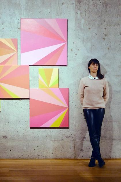 Portraitfoto von Carla Bertone, vor einer beigen Wand, neben ihr fünf ihrer Werke in Rosa, Gelb und Grün