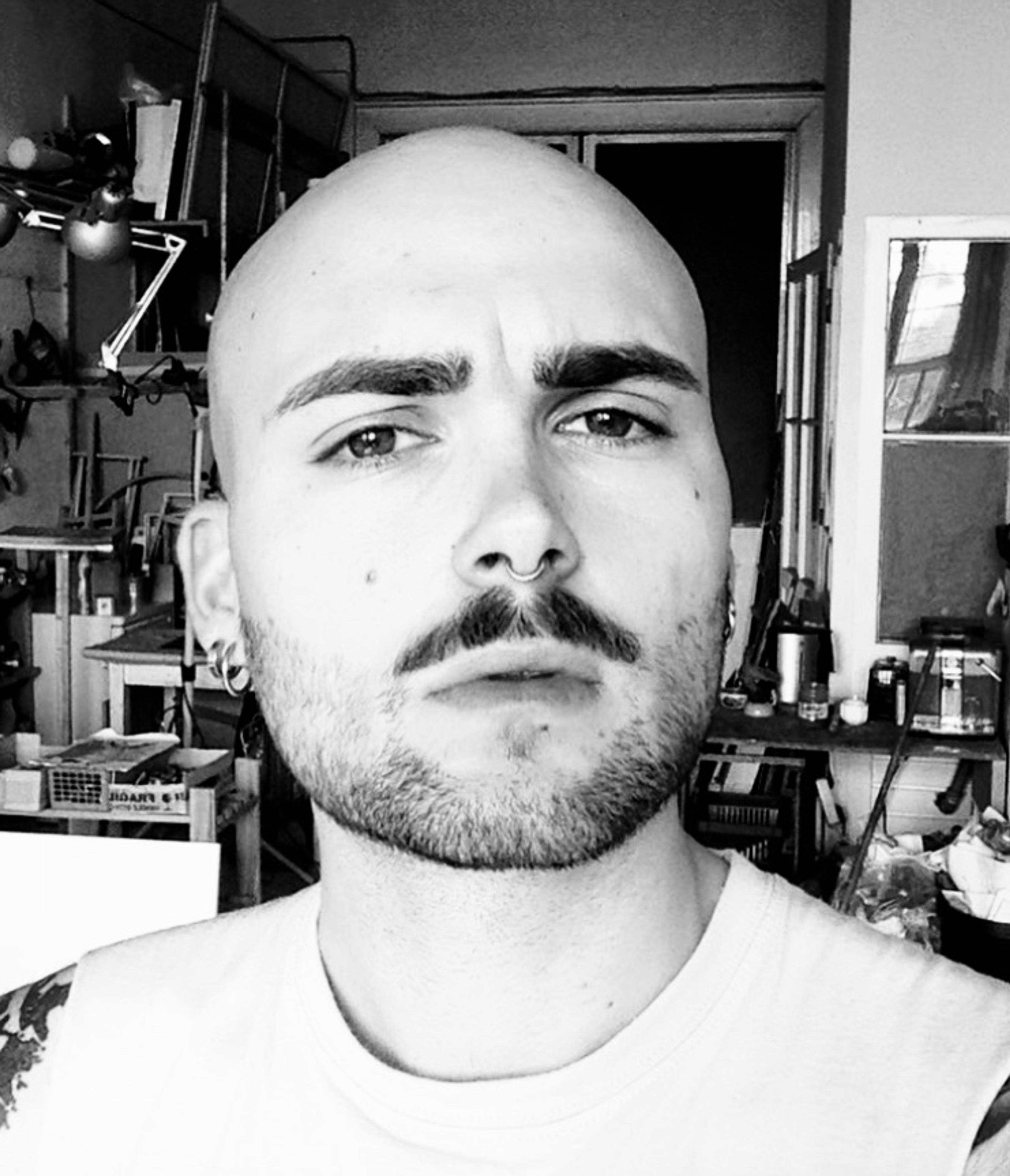 Schwarz weiß Portraitfoto des Künstlers Niklas Jeroch in seinem Atelier
