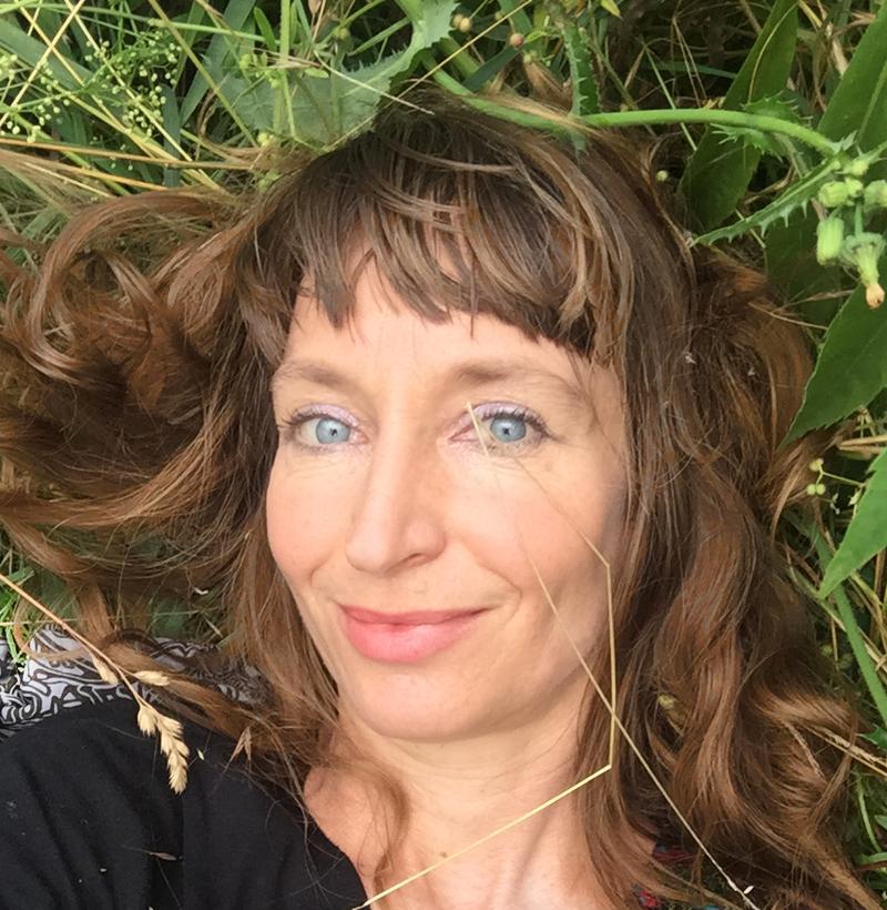 Portraitfoto der Künstlerin Eva Lippert, liegend im Gras