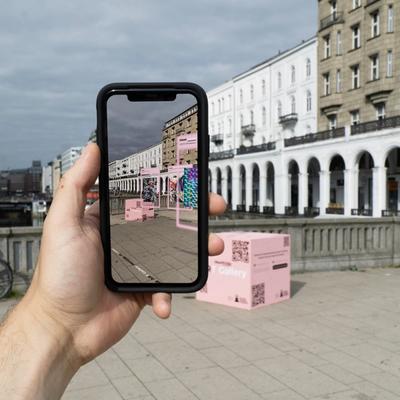 Eine Hand hält ein Smartphone. Im Hintergrund ist die Reesendammbrücke und ein pinker Würfel mit QR-Codes zu sehen. Auf dem Smartphone ist die Kamera aktiviert, der Bildschirm zeigt die Reesendammbrücke und den Kubus mit einer AR-Gallery.