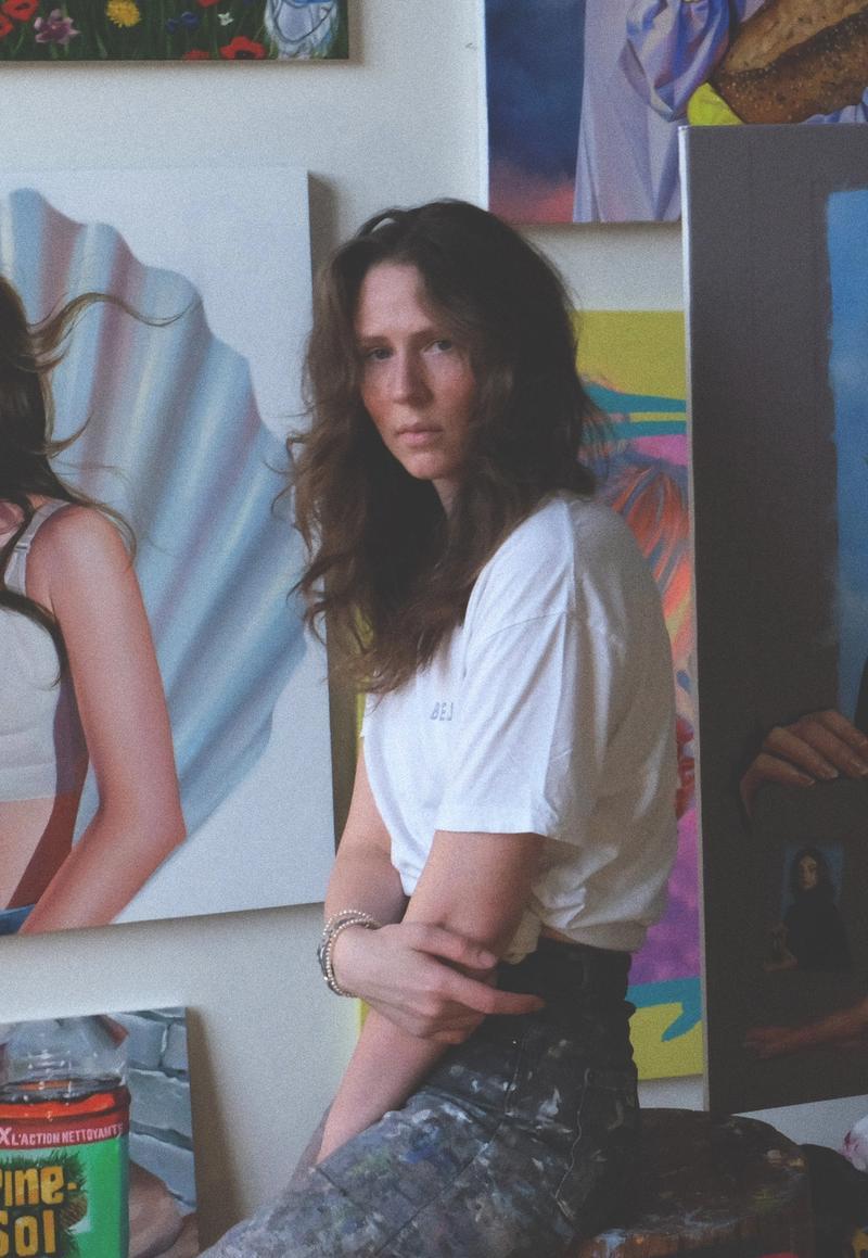 Portraitfoto der Künstlerin Roxanne Suariol, in ihrem Studio, vor figurativen Malereien
