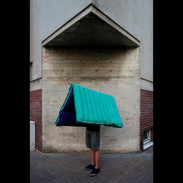 Ein Foto von einer Person, über dessen Kopf eine halbaufgeblasene Luftmatratze hängt.