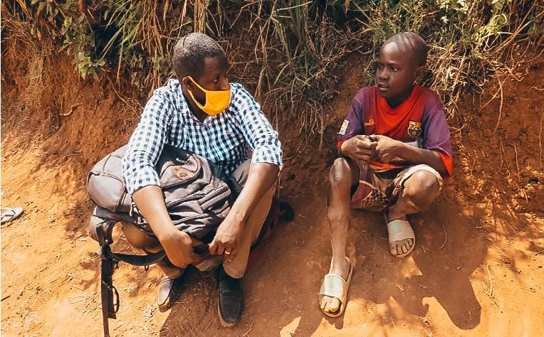 two kids sitting outside in Rwanda wearing masks