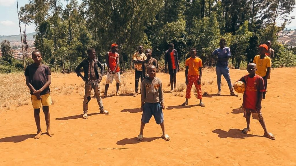 group of kids in Rwanda standing outside holding a soccer ball