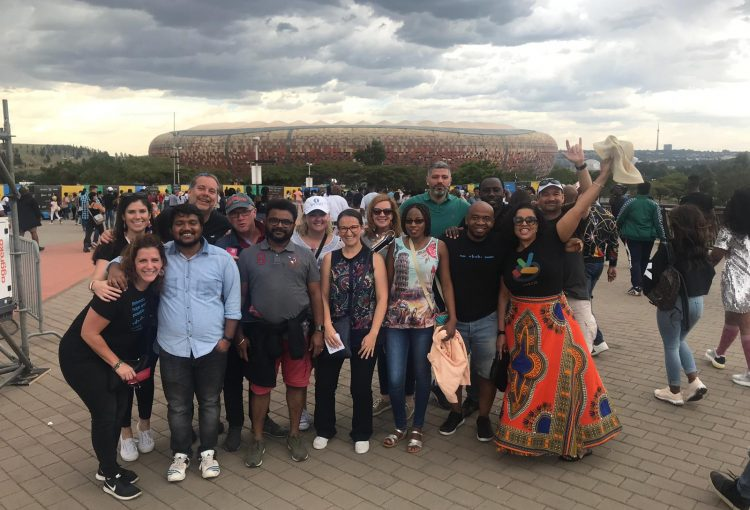 Group of award winners standing together outside a stadium in South Africa