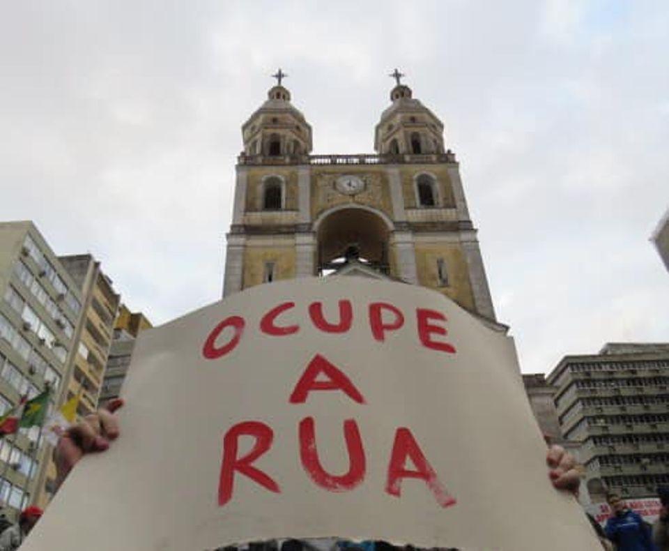 Manifestante segura cartaz em frente a Catedral de Florianópolis